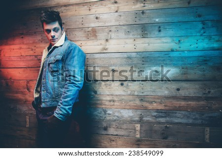 Winter jeans fashion man with short dark hair. Wearing jeans jacket, trousers and brown leather gloves. Leaning against old wooden wall. - stock photo