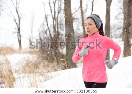 Winter jogging - young Asian Chinese adult woman runner running breathing cold air wearing pink windbreaker jacket, headband and gloves doing a cardio workout. - stock photo
