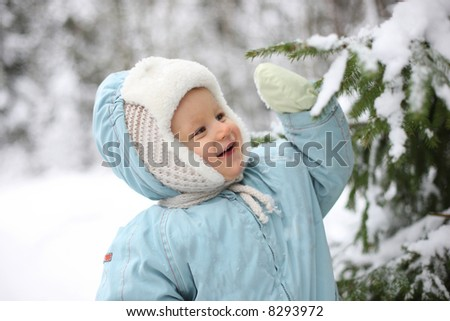 Winter joy - small kid stands next to snowy tree - stock photo