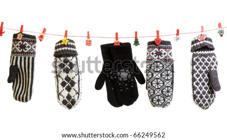 Winter knitted gloves hang on the Christmas lights in the clothes pins - stock photo
