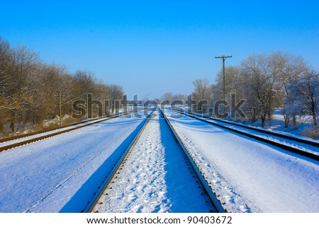 Winter landscape along the railway line Three railroad tracks with lots of fresh snow and icy trees. - stock photo