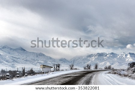 Winter landscape, an icy road leading towards Ala-Archa national park, Kyrgyzstan with dramatic mountains and sky in the background.  - stock photo