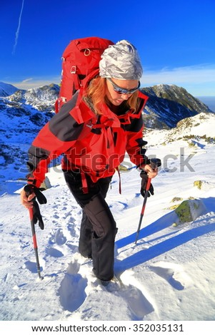 Winter landscape and woman backpacker on snow covered trail, Retezat mountains, Romania