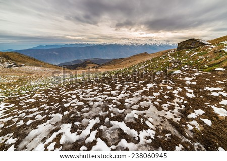 Winter landscape at sunset over alpine valley and snowcapped mountain range with old pasture hut. Frozen pattern on the ground and cold feeling. Italian Alps. - stock photo