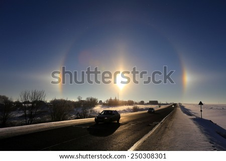 winter landscape beautiful solar halo over the desert road going over the horizon - stock photo