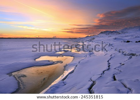 winter landscape beautiful sunset over the river covered with ice and the city on the horizon  - stock photo