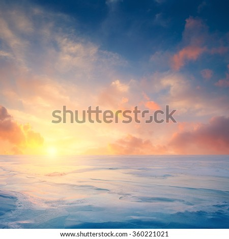 Winter landscape. Frozen sea and fantastic sunset sky. Sunlight reflected on the ice - stock photo