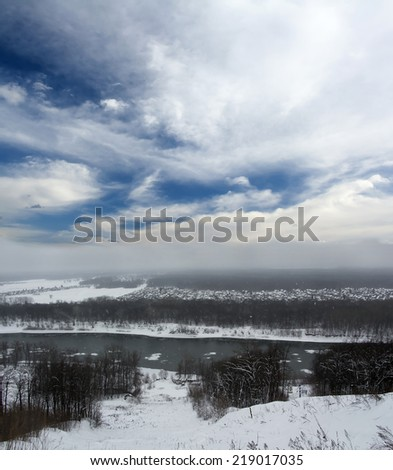 Winter landscape. Gray snowy forest and blue sky with white clouds. Cold river. Snow - stock photo