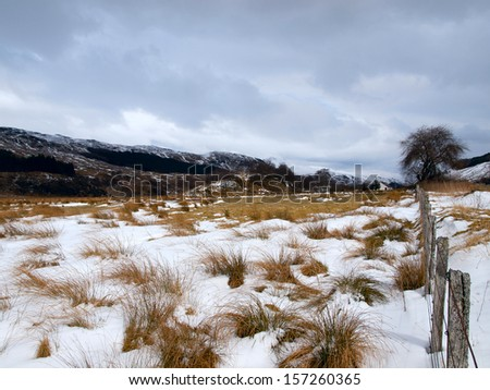 Winter landscape in Crianlarich in the Scottish Highlands with a dark gloomy sky - stock photo
