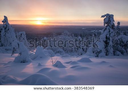 Winter landscape in Lapland Finland on sunset. Photo taken on mountain near popular tourist ski resort. - stock photo