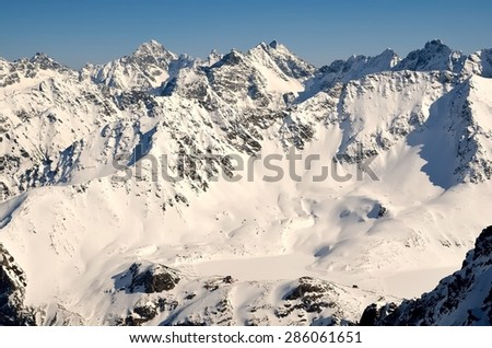 Winter landscape in mountains. View from the ridge over frozen lake in the valley and snowy summits, National Park in High Tatra Mountains. - stock photo