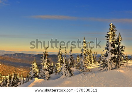 Winter landscape in the mountains at sunset. The mountain slopes are covered with coniferous forest and illuminated soft light of the setting sun. Fabulous winter nature - stock photo