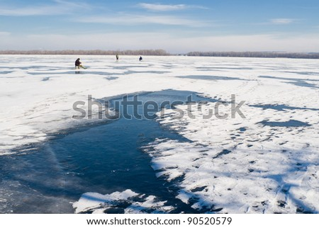 Winter landscape - lonely fishermans on a frozen river.
