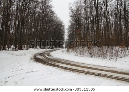 winter landscape of bare forest and dirty road turning right - stock photo