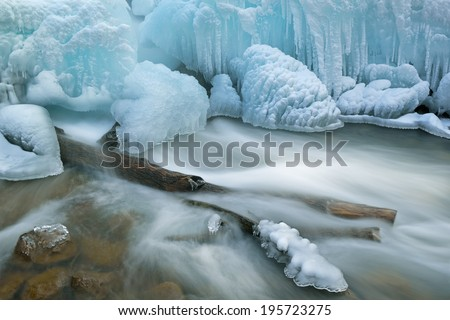 Winter landscape of cascade captured with motion blur and framed by blue ice, Gull Creek, Michigan, USA  - stock photo