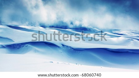 Winter landscape of high mountains with snow blizzard and fresh blue sky, beautiful nature panoramic background - stock photo