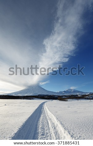 Winter landscape of Kamchatka: snowmobile track to eruption active Klyuchevskoy Volcano (Klyuchevskaya Sopka) - emission from crater of volcano plume of gas, steam and ashes. Eurasia, Russian Far East - stock photo