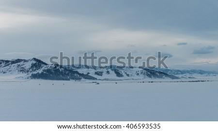 Winter landscape of snow-capped mountains. Dusk. Clouds. A snowy field. - stock photo