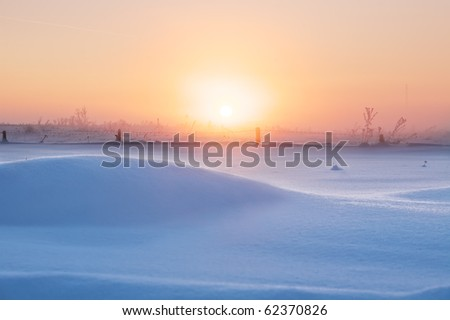 Winter landscape of snow field with snowdrift on sunset background - stock photo
