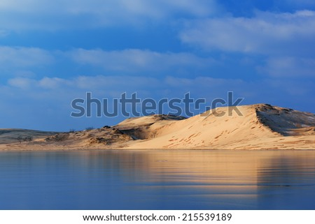 Winter landscape of the Silver Lake Sand Dunes reflected in frozen Silver Lake, Silver Lake State Park, Michigan, USA  - stock photo