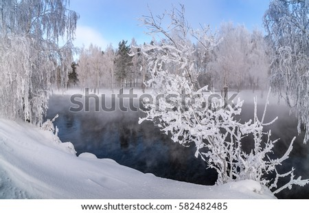 winter landscape on a river with fog and trees in the frost of Russia, the Urals, February