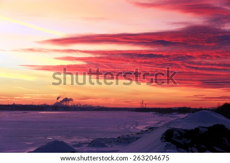 winter landscape red sunset on the ice of the river and and pipe plant on the horizon - stock photo