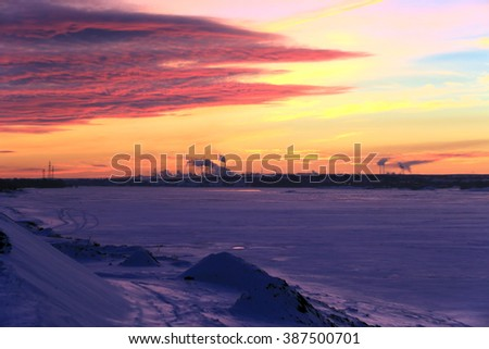 winter landscape red sunset on the ice of the river and and pipe plant on the horizon