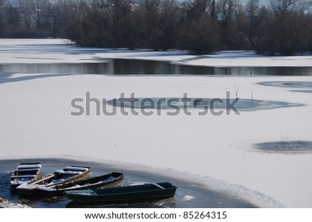 Winter landscape. Small frozen river and boats  on ice