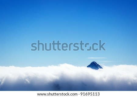 Winter landscape - snowed mountain's top over white clouds cover and clear blue sky background - stock photo