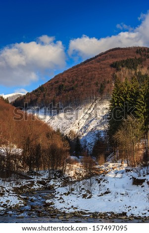 winter landscape. stream flows between the mountains covered with snow. on the mountains grows forest of deciduous trees and some conifers - stock photo