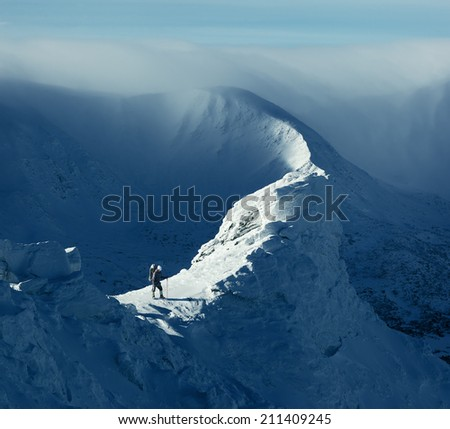 Winter landscape. Sunny day in the mountains. Tourist standing on a rock - stock photo