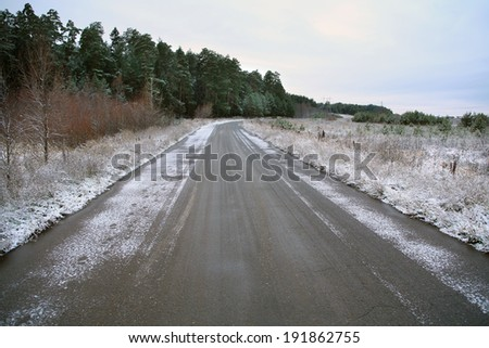 winter landscape  the first snow in field near forest and road on a cloudy day - stock photo
