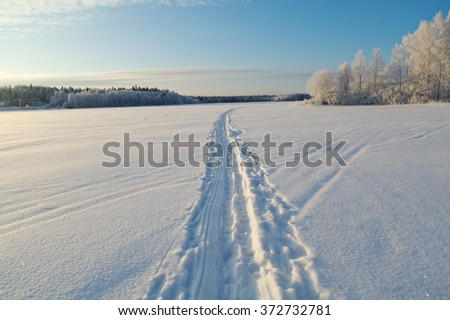 Winter landscape.trace of a snowmobile on frozen lake - stock photo