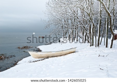 Winter landscape with a fishing boat on seacoast - stock photo