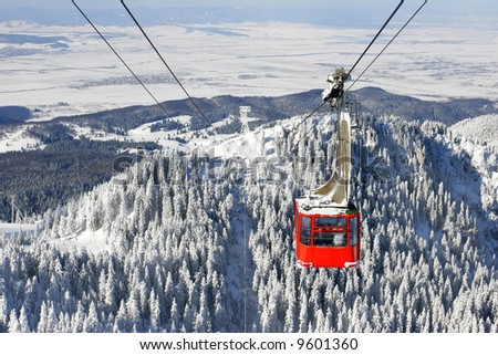 Winter landscape with a red cable car. - stock photo