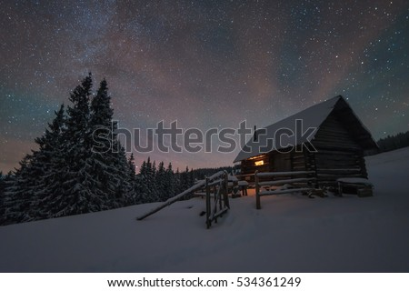 Winter landscape with a starry sky. The light in the cabin in the mountains
