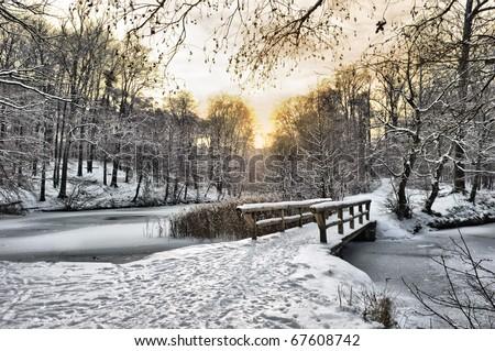 Winter landscape with a wooden bridge - stock photo