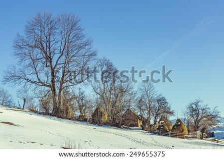 Winter landscape with ancient Romanian farm on a sunny morning in Magura village, Brasov county, Romania. - stock photo