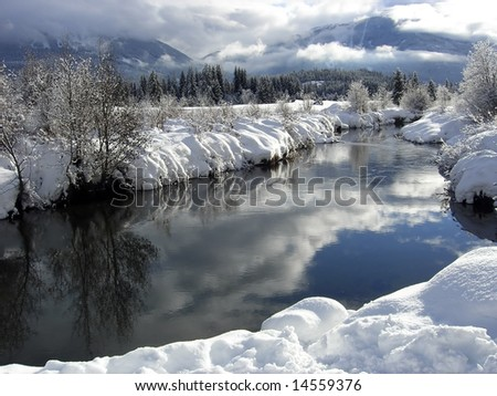 Winter landscape with blue sky reflecting in a river near Whistler - stock photo