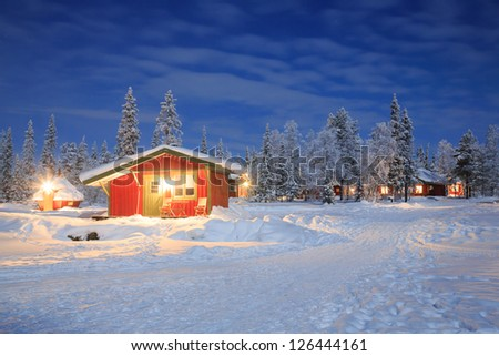 Winter landscape with cabin hut at night in Kiruna Lapland Sweden at Night with star trail - stock photo