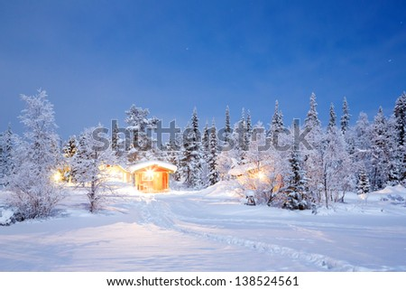 Winter landscape with cabin hut at night in Kiruna Sweden at Night with star trail - stock photo