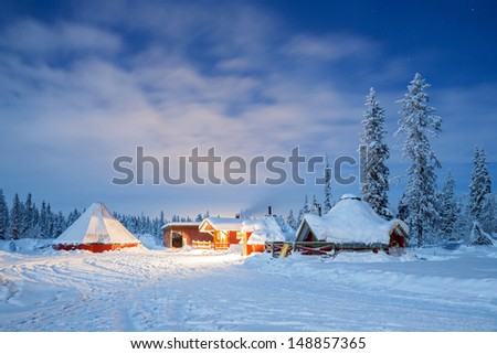 Winter landscape with cabin hut at night in Kiruna Sweden lapland at Night with star trail - stock photo