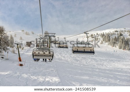 Winter landscape with chairlift and slope at alpine ski resort - stock photo