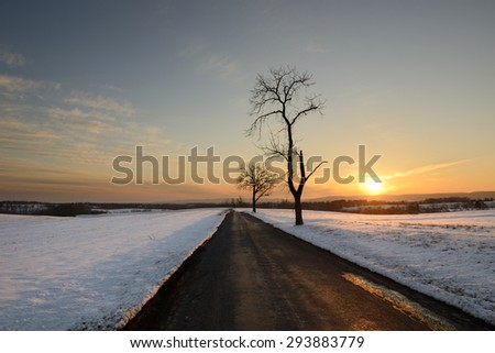 Winter Landscape with Country Road and Snow at Sunset - stock photo