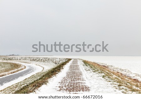 Winter landscape with dike covered with snow and frozen sea, Marken, the Netherlands