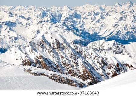 Winter landscape with lopes on a skiing resort in the Alps with mountains background - stock photo
