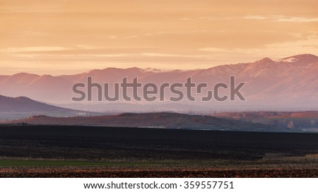Winter landscape with mountain and ploughed land at sunset light - stock photo