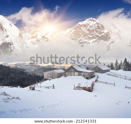 Winter landscape with mountain villages. Wooden houses on a snowy meadow. Carpathian mountains, Ukraine, Europe - stock photo