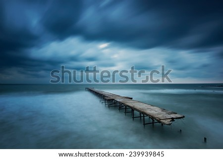 Winter landscape with old broken bridge among the stormy sea - stock photo