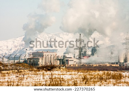 Winter landscape with refinery and smoky industrial background - stock photo